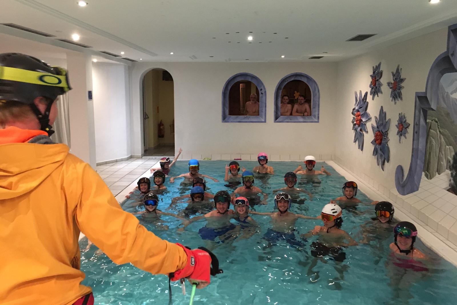 Skigruppe mit Helmen im Pool