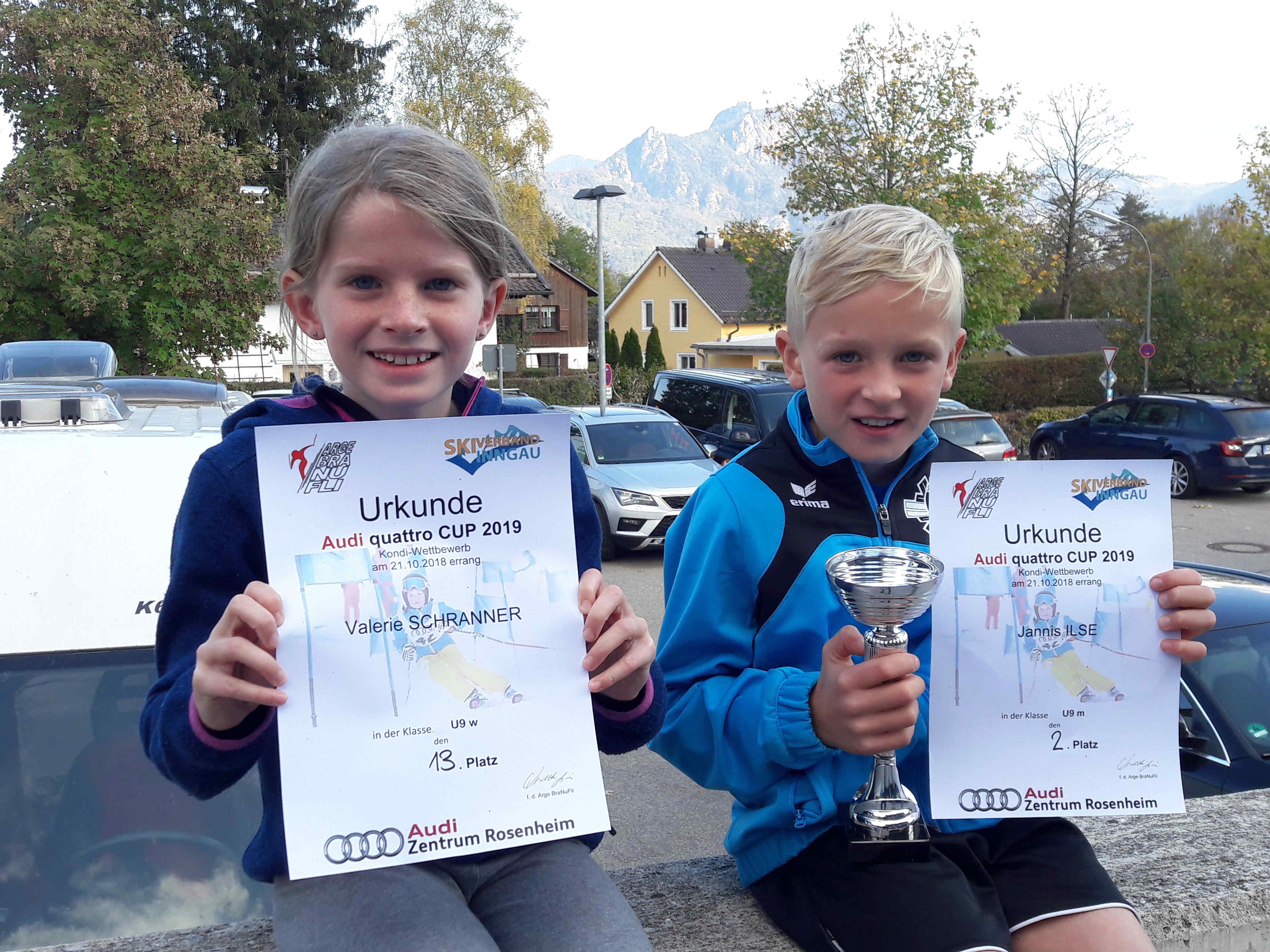 Zwei Kinder präsentieren ihre Urkunden und Pokale