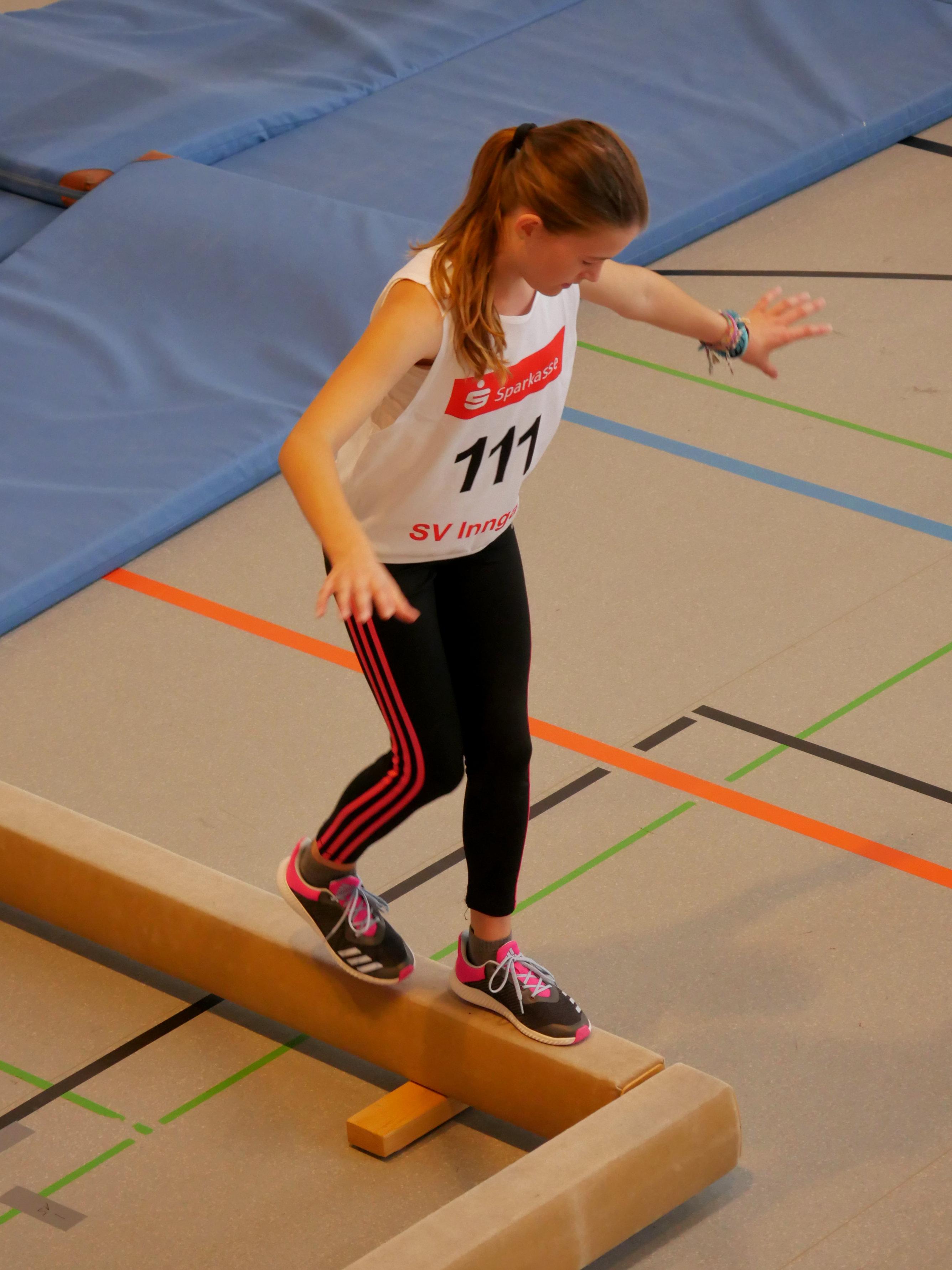 Sportler balanciert auf einem Schwebebalken